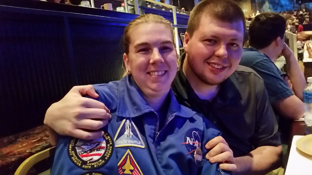 Anneliese, smiling, dressed in a NASA flight jacket, sits beside her husband, Derek, also smiling, who has his right arm gently draped about her right shoulder and his left hand on her left shoulder