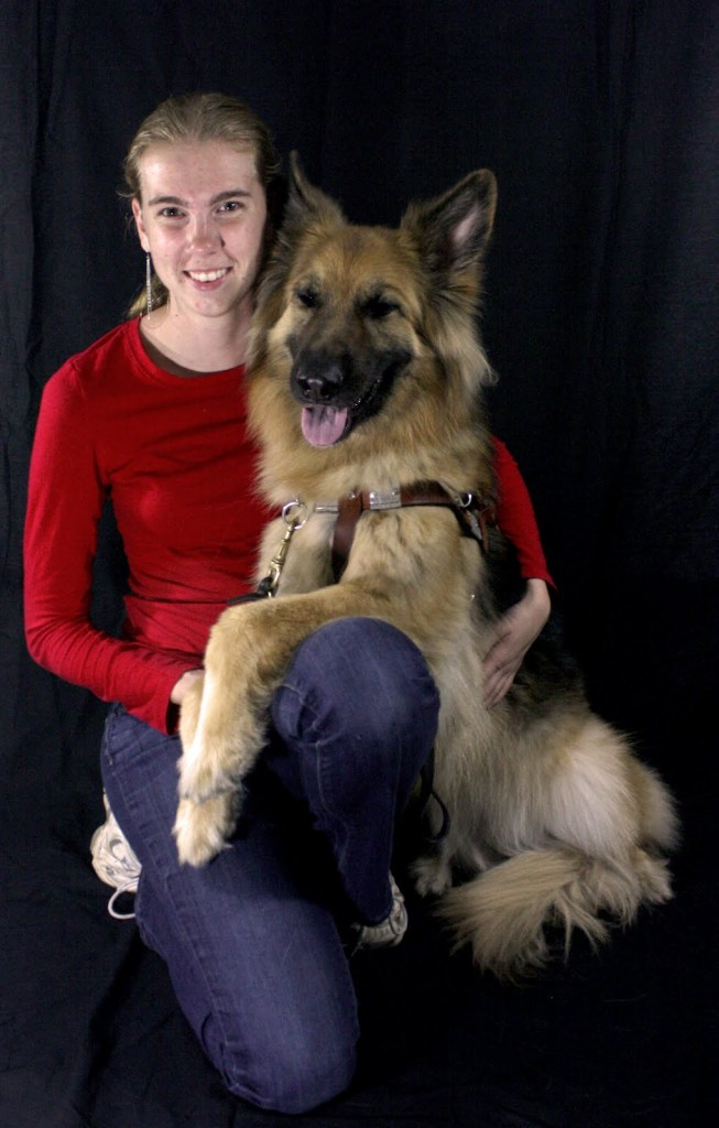 Anneliese, smiling, half kneeling and sitting on her right heel, holds Prada, also smiling, with her front paws draped over Anneliese's left leg)