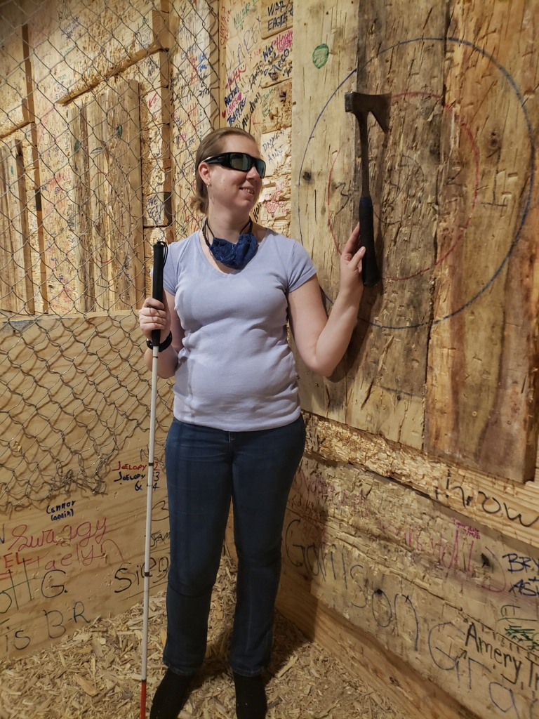 Anneliese, wearing a grey v-neck t-shirt, jeans, and sunglasses, stands holding her cane next to a 2x2 layered plywood target mounted on a concrete wall. An axe sticks out from the central ring painted on the target.