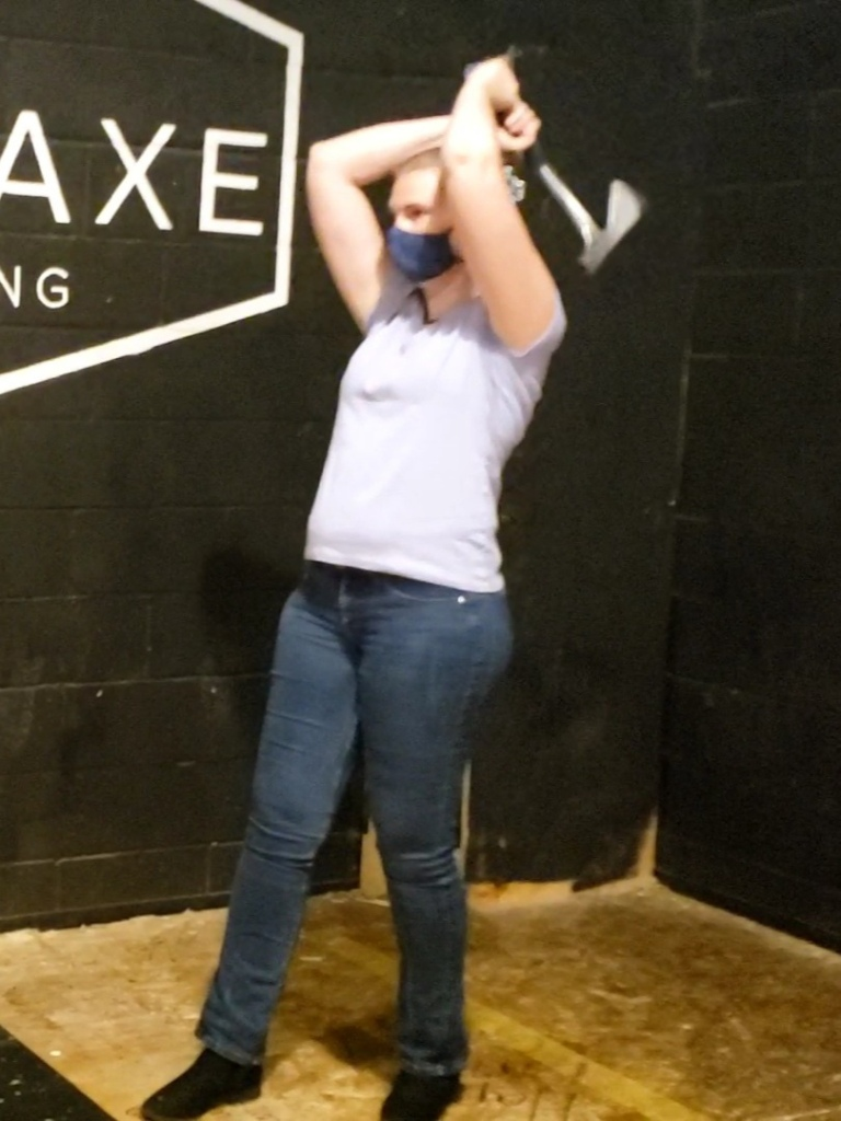 Anneliese, in the same outfit as above, sans shades and cane, stands with an axe gripped in both hands and cocked over her head as she prepares to throw it at a target not visible in the photo.