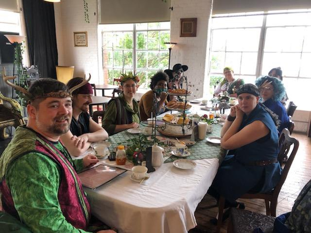 Half a dozen people in fantasy-style medieval costumes sit around a wooden table. Anneliese, in a long blue vest and faun antlers, is on the right, facing the camera.